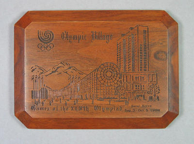 """Brown Wooden """"Olympic Village"""" Plaque in White Box"""
