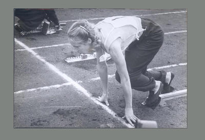 Photograph of Shirley Strickland positioned on starting blocks, c1955