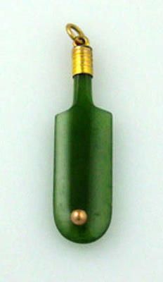 Jade pendant shaped as a cricket bat with gold ball