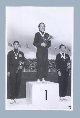 Photograph of 100m place getters on podium, International Friendly Sports Meeting of Youth 1955
