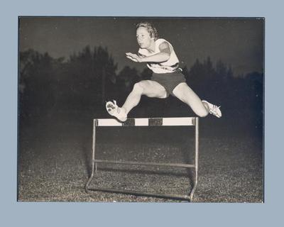Photograph of Shirley Strickland leaping over a hurdle, c1956