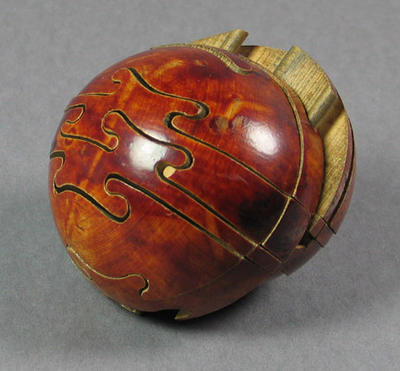 Wooden puzzle shaped as a cricket ball  c. 1910