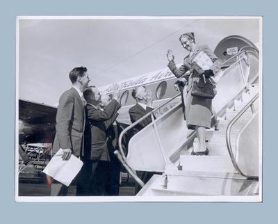 Photograph of Shirley Strickland on aeroplane steps with Greater Union staff, 1957
