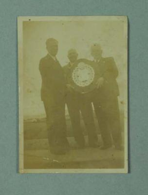 Small black and white photograph of three  men holding the Claxton Shield