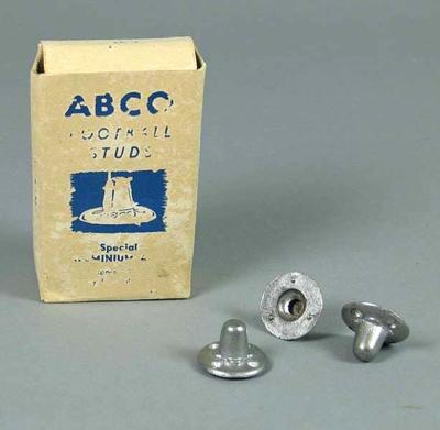 Football boot studs in cardboard box, c1960