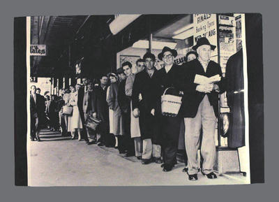 Photograph of people standing in line waiting to buy tickets, undated