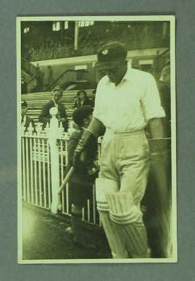 Photographic Postcard:  Don Tallon walking on to the  MCG pitch December 1938