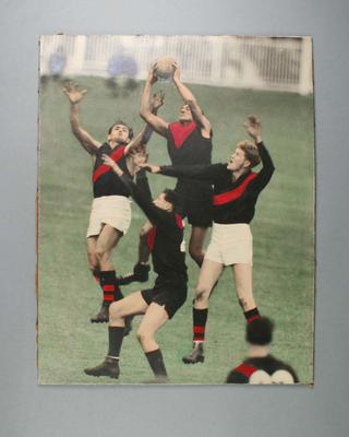 Hand- coloured photograph of four footballers leaping for a mark