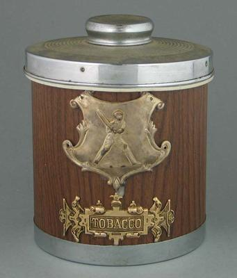Tobacco jar with lid attached metal shield showing  cricketer preparing to bat.