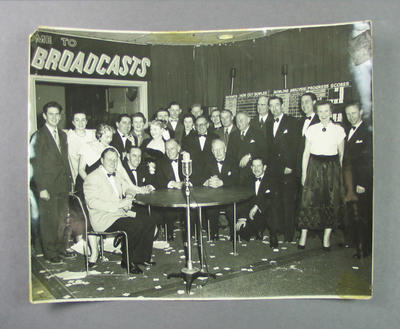 Photograph, depicts 3AW broadcast studio with a group of people, cricket score board in background