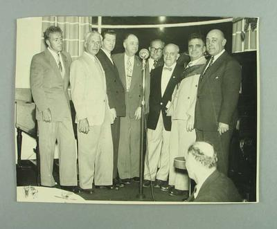 Photograph of eight men dressed in suits at a formal event, c1970s