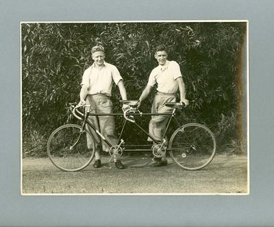Black and white photograph of Ernie Milliken and Wally Stuart standing beside their tandem at BSA Testing Track 1935