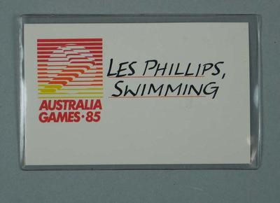 Identification card in plastic sleeve. Logo of Australia Games 1985; handwritten Les Phillips, Swimming; Documents and books; 1986.1265.4