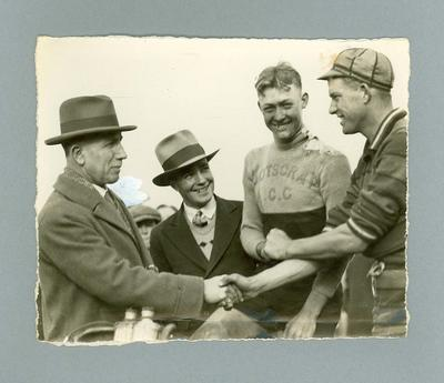 Photograph of Chris Wheeler in Footscray ACC shirt 1936, shaking hands with ors.