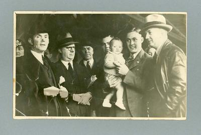 Photograph of Chris Wheeler  holding a baby amongst a group of people c. 1930s