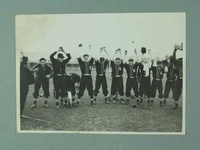 Black and white photograph, 1947 Victorian State Baseball team and officials, with arms up
