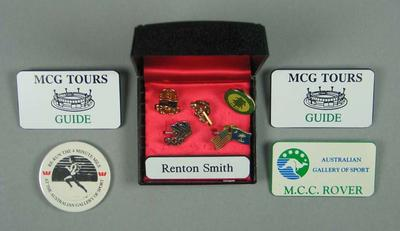 Group of ten assorted badges and pins worn by Renton Smith, a former AGOS volunteer Guide
