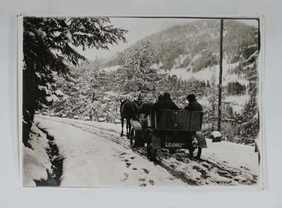 Reproduction of black & white photograph depicting a horse drawn cart travelling through snow, with three passengers