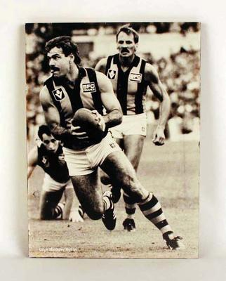 A mounted black and white action photograph of Leigh Matthews, of the Hawthorn Football Club; Photography; M16008