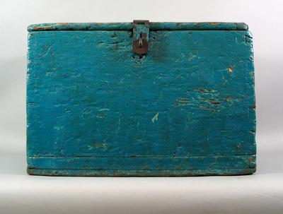 Blue painted wooden trunk with large metal hinges, handles on two sides