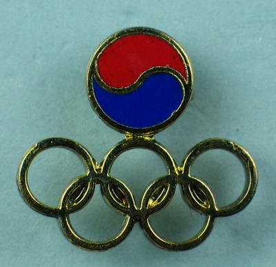 Tie tack, gold Olympic rings with red & blue disc