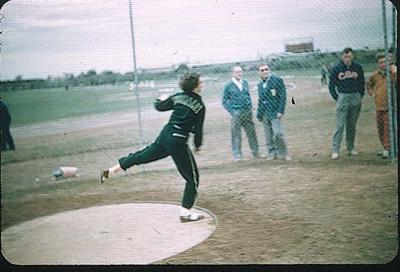 Colour slide taken during the 1956 Olympic Games, shows an athlete wearing a tracksuit throwing a discus on an open playing field