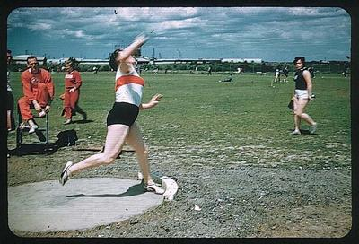 Colour slide taken during the 1956 Olympic Games, shows an athlete throwing a shot on an open playing field