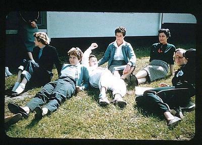 Colour slide of six female athletes, sitting outside a building, in 1956 Olympic Village