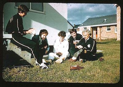 Colour slide of five female athletes, sitting outside a building, in 1956 Olympic Village