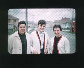 Colour slide of three female athletes, in United States team uniform, outside 1956 Olympic Village