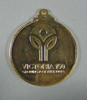 Commemorative gold medal in plastic pouch;  'Australia Games 85' and 'Victoria 150' logos stamped on medal