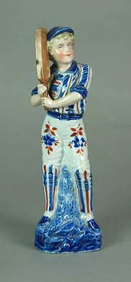 Ceramic Delft-style figurine depicting boy with cricket bat