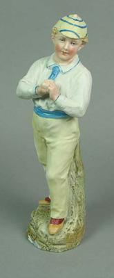 Painted bone china figurine of a boy cricketer holding a cricket ball