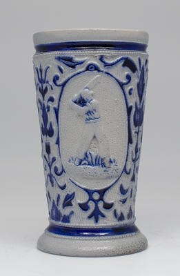 Ceramic cup bearing blue and white cricketers and foliage design