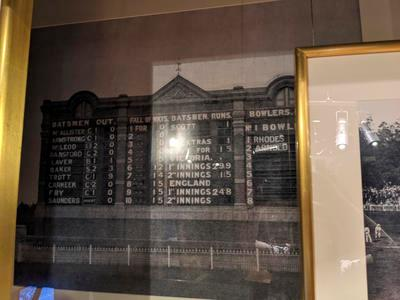 Framed, mounted black and white photo reproduction of the MCG Scoreboard taken during a match between Victoria and the Marylebone Cricket Club on 9 February, 1904