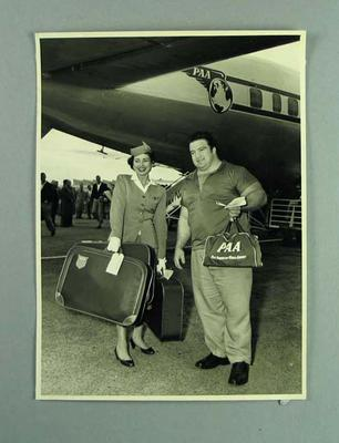 Photograph of Paul Anderson with PAA air hostess Deborah Joselson, 1956