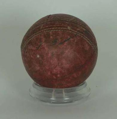 Red leather cricket ball autographed by Clarrie Grimmett.