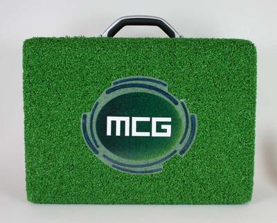 Astro turf covered briefcase with MCG logo.