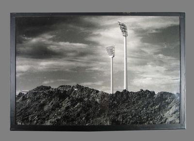 Photograph of two MCG light towers rising out from a pile of dirt