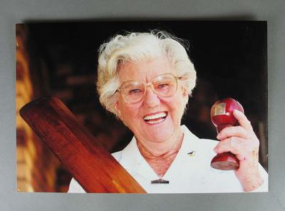 Colour photograph of Betty holding the bat and ball from her famous test match.