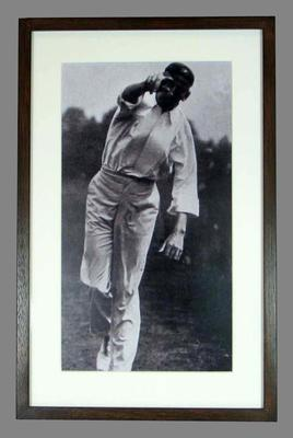 Framed black and white reproduction photograph of Hugh Trumble bowling