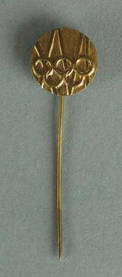 Gold coloured reproduction pin from the 1956 Olympic Games.