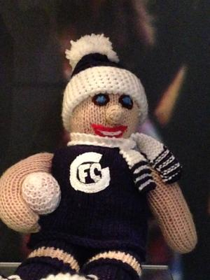 Knitted doll in Carlton Football Club attire, with No. 13 verso