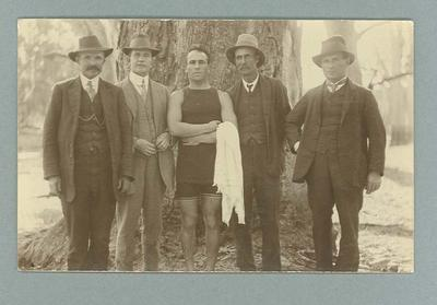 Postcard featuring a man in a swimming suit standing with four men in suits, pictured in front of a tree