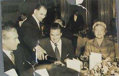 Photograph of Keith Miller enjoying lunch at the Connaught Rooms, 27 April 1956