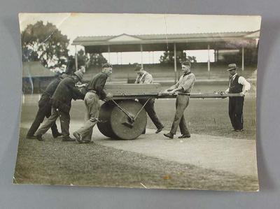 Black and white photograph of Albert Luttrell  and groundsmen, rolling the cricket pitch at the MCG