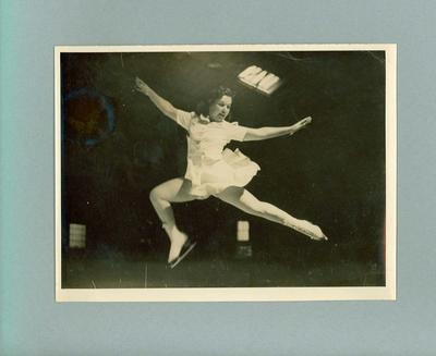 Photograph - Betty Cornwell  in a mid air leap, on indoor ice rink.