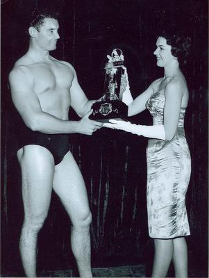 """Photograph of Tom Lardner being presented with """"Mr Australia"""" trophy, 1959"""