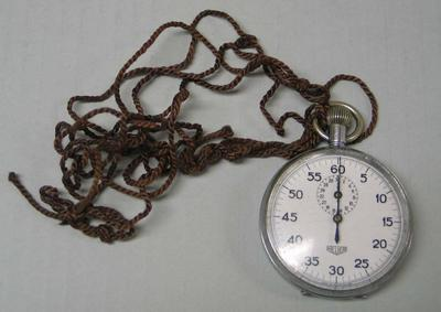 Circular stopwatch with round white face and brown cord, rating table on reverse