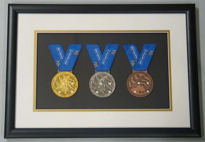 Three framed un-awarded Deaflympic Games medals presented to Minister for Sport, Justin Madden, 2005